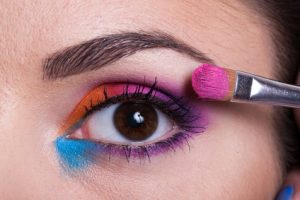 Makeup artist applying bright purple, orange and blue makeup to the white caucasian brunette girl